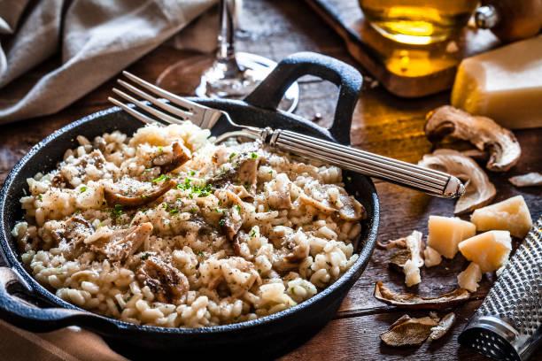risotto pilze steinpilz auf rustikalen holztisch - pilzpfanne stock-fotos und bilder
