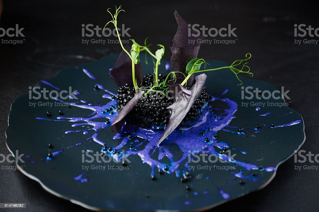 Risotto with cuttlefish ink and black caviar stock photo