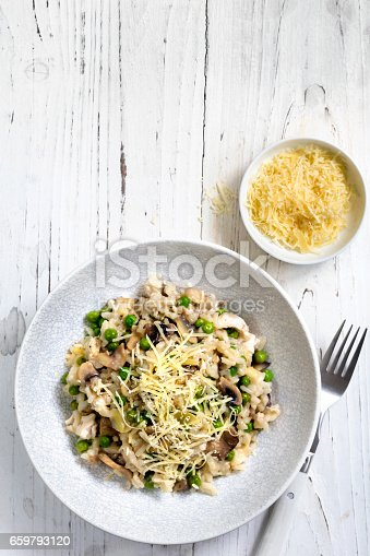 Risotto with mushrooms and peas, topped with grated parmesan.  Top view, over distressed white timber.