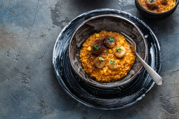 Risotto with pumpkin and scallops, on stone background, copy space stock photo
