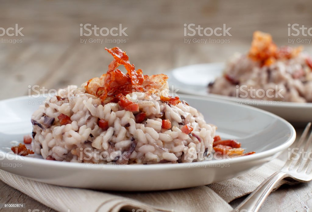 Risotto with red radicchio and crispy bacon (speck) stock photo