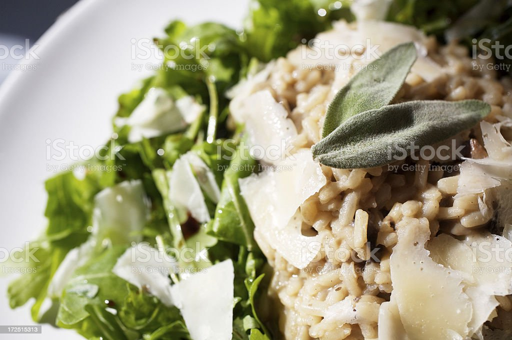 Risotto with rocket leaves, parmesan cheese flakes and sage stock photo