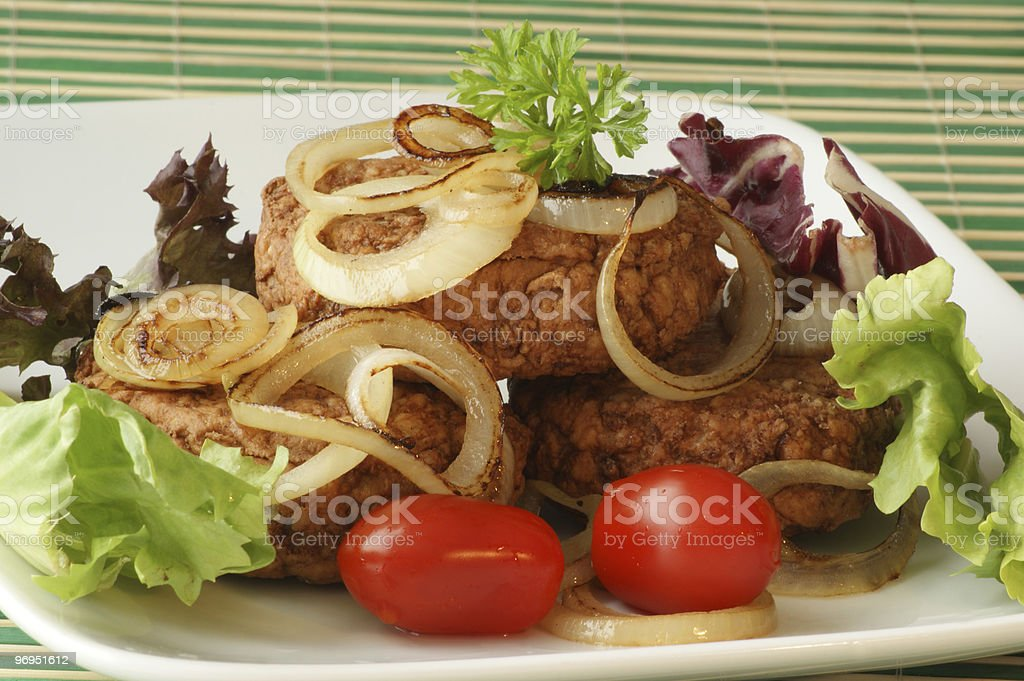 rissole with grilled organic onion and parsley on a plate royalty-free stock photo