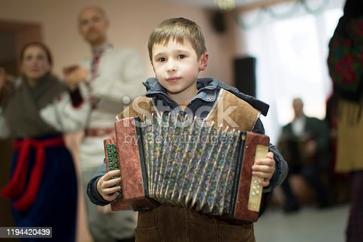 Rite of a generous evening. Kalyada ceremony. Village child with Russian accordion