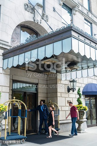 New York City, USA - July 28, 2018: Entrance of the Ritz Carlton New York Hotel, next to Central Park, with a black bellboy opening the door to some customers in Manhattan, New York City, USA