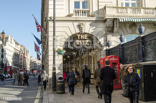 LONDON, UK - JANUARY 28, 2016:  Pedestrians and traffic at the Ritz Hotel arcade in Piccadilly, London on a sunny winter afternoon in central London.