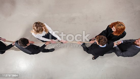 Rival business man and woman compete in office for the command by pulling the rope