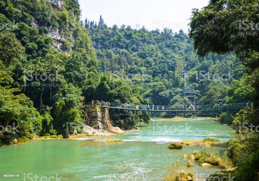 River and suspension bridge in China Huangguoshu scenery park stock photo