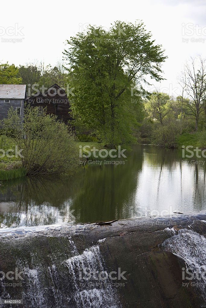 River and waterfall near farm house royalty-free stock photo