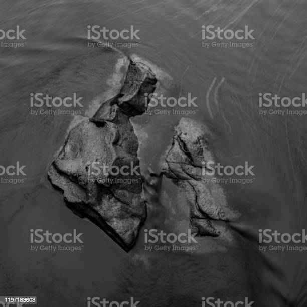 Photo of River Boulders Peek Above Rushing Water