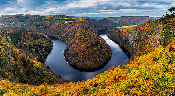 river canyon with dark water and autumn colorful forest - tsjechië stockfoto's en -beelden