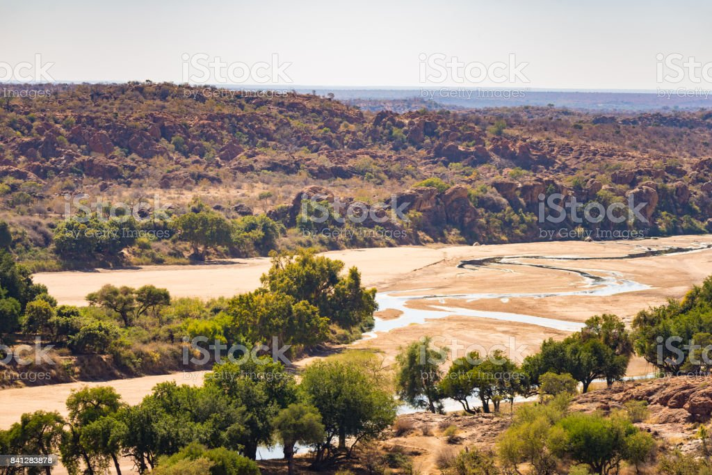 River crossing the desert landscape of Mapungubwe National Park, travel destination in South Africa. Braided Acacia and huge Baobab trees with red sandstone cliffs. stock photo