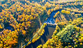 Scenic view on the meandering river next to rural road among a trees in bright yellow foliage. Aerial view on nature landscape at a sunny autumn day