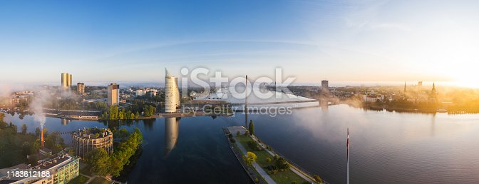River Daugava photographed at sunrise. The Swedbank building called Saules Akmens is in the foreground. AB dambis pier and Kliversala district can also be seen. Old Town Riga is in the background