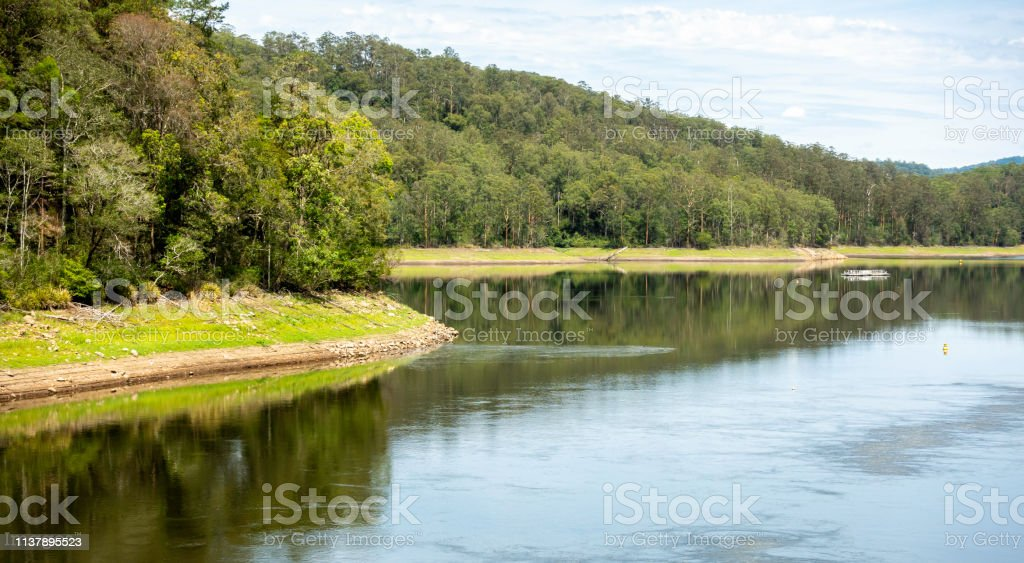 River flowing gently by natural woodlands stock photo