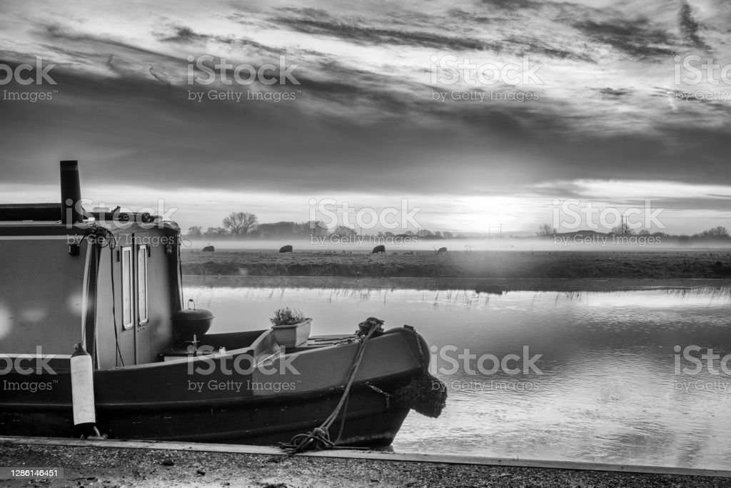 River Great Ouse at sunrise Sunrise over the Great Ouse River at Huntingdon, Cambridgeshire, England, UK. There is mist on the fields in the background and a narrowboat moored in the foreground. 2020 Stock Photo