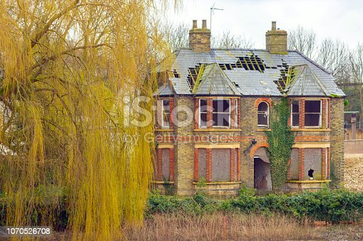 River Great Ouse in flood at Godmanchester with a derelict large Victorian house in the foreground.