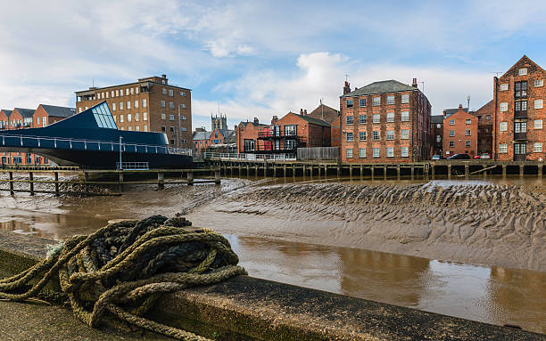 river hull with bridge, flats, and church on the horizon. - hull stock pictures, royalty-free photos & images