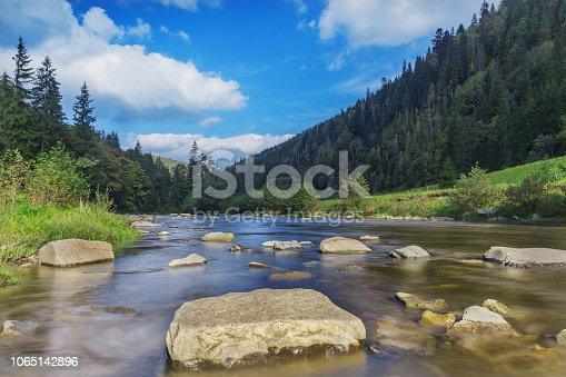 River in mountains with rocks, green grass on riverside. Mountain landscape, beautiful sky, clouds. Idea for outdoor activities, travel .