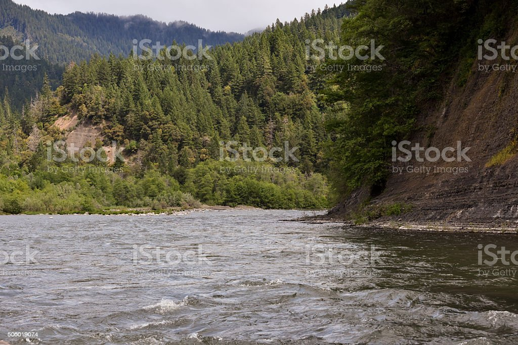 river in rugged forestland seen from boat stock photo