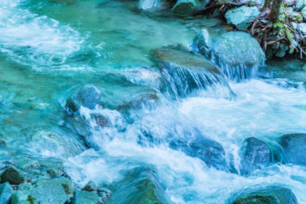 rivier in de bergen achter de stroom van het rijke water - stroom stromend water stockfoto's en -beelden
