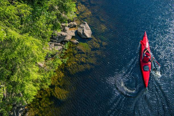 River Kayaker Aerial View River Kayaker Aerial View. Caucasian Sportsman in the Red Kayak Paddling on the Scenic River Along the Shore. canoeing stock pictures, royalty-free photos & images