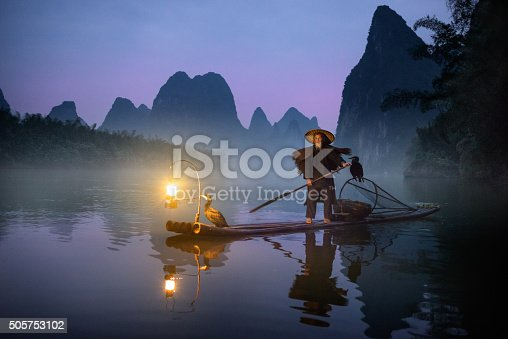 River Lee Cormorant Fisherman on bamboo raft with two cormorant birds and illuminated petrol lantern. Shot at dawn, mountains in the background.