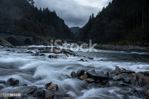 River near Latefossen waterfall on long exposure in dark cloudy moody weather light. Soft silky water in the Odda valley, Norway
