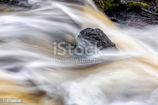 Long exposure of raging river , stone surrounded by churning water