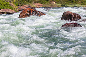 River rocks rapids with raging water power closeup rural valley landscape.