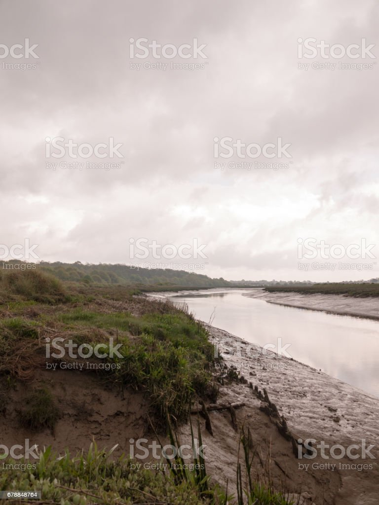 rivière qui coule à travers la campagne sur une journée nuageuse photo libre de droits