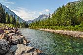 A river runs calmly through a valley in Glacier National Park of Montana.