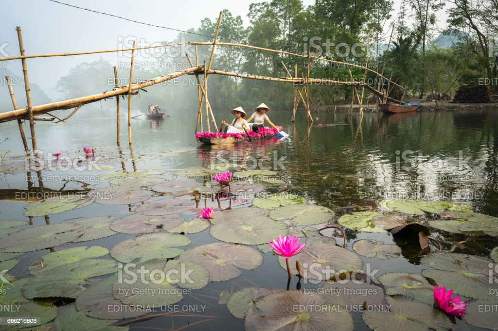 Ninh Binh, Vietnam - Oct 9, 2016: River scene with smoke, a boat carrying girls wearing traditional dress Ao Dai, conical hat, and flower stock photo