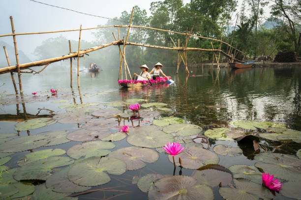 ninh binh, vietnam - oct 9, 2016: river scene with smoke, a boat carrying girls wearing traditional dress ao dai, conical hat, and flower - ao dai stock photos and pictures