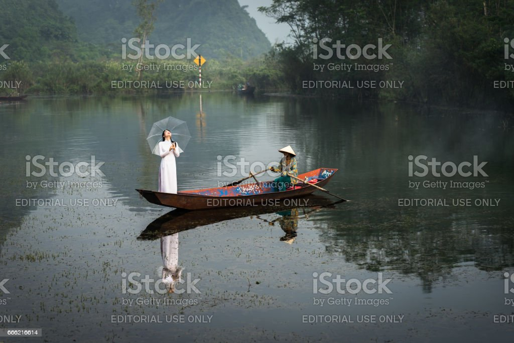 Ninh Binh, Vietnam - Oct 9, 2016: River scene with tourist boat carrying girls wearing traditional dress Ao Dai, conical hat stock photo
