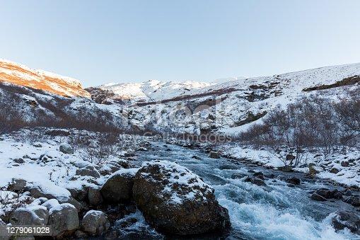 River in a snowy field in Glymur, Iceland