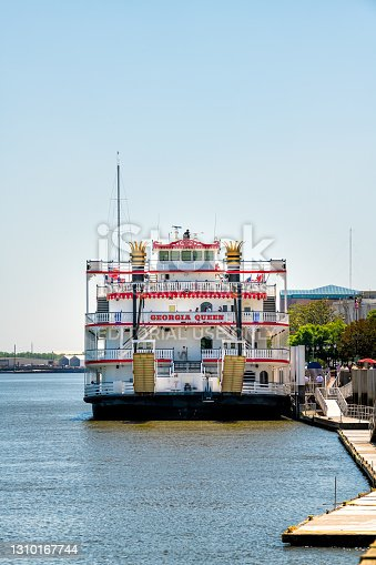 Savannah, USA - May 11, 2018: River street old town waterfront with Georgia Queen steamboat cruise ship belles ferry with people in southern town city