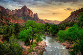 The Virgin River flowing through Zion Canyon with the peak of The Watchman mountain as a backdrop in Zion National Park, Utah, at dusk.