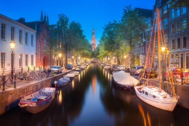 rivier, traditionele oude huizen en boten, amsterdam - westerkerk stockfoto's en -beelden