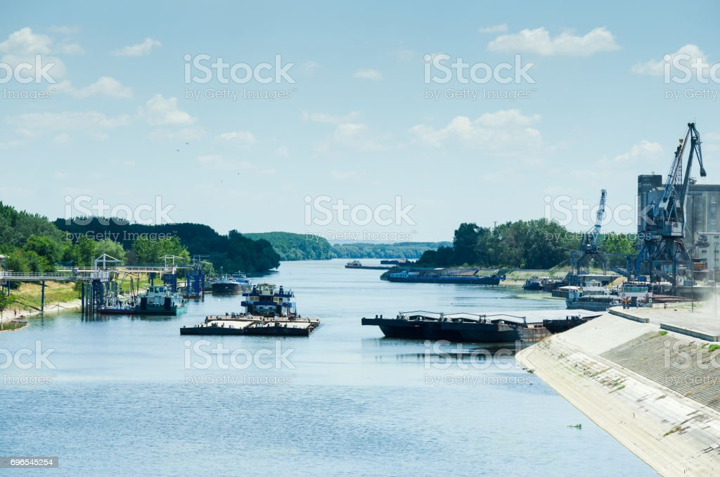 River tugboat moves cargo barge in the channel. stock photo