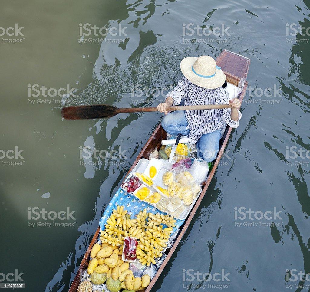 River vendor selling fruits along Thailand floating market stock photo
