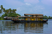 River view and traditional house boat in Kerala's Backwaters, India.
