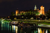 Krakow, Poland - August 22, 2017:River Vistula with barges restaurants, recreational ship and the Royal Castle on Wawel Hill by night in the city of Krakow in Poland. Wawel Royal Castle inscribed on the UNESCO World Heritage List.