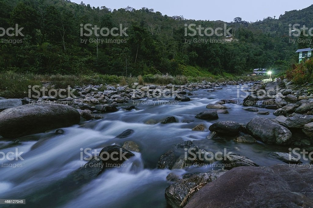 River water flowing through rocks at dusk royalty-free stock photo