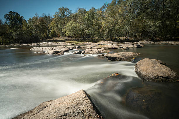 river with a small waterfall and forest on the banks the South Tyger River in South Carolina with rocks and a small waterfall in the foreground and trees in the background spartanburg stock pictures, royalty-free photos & images
