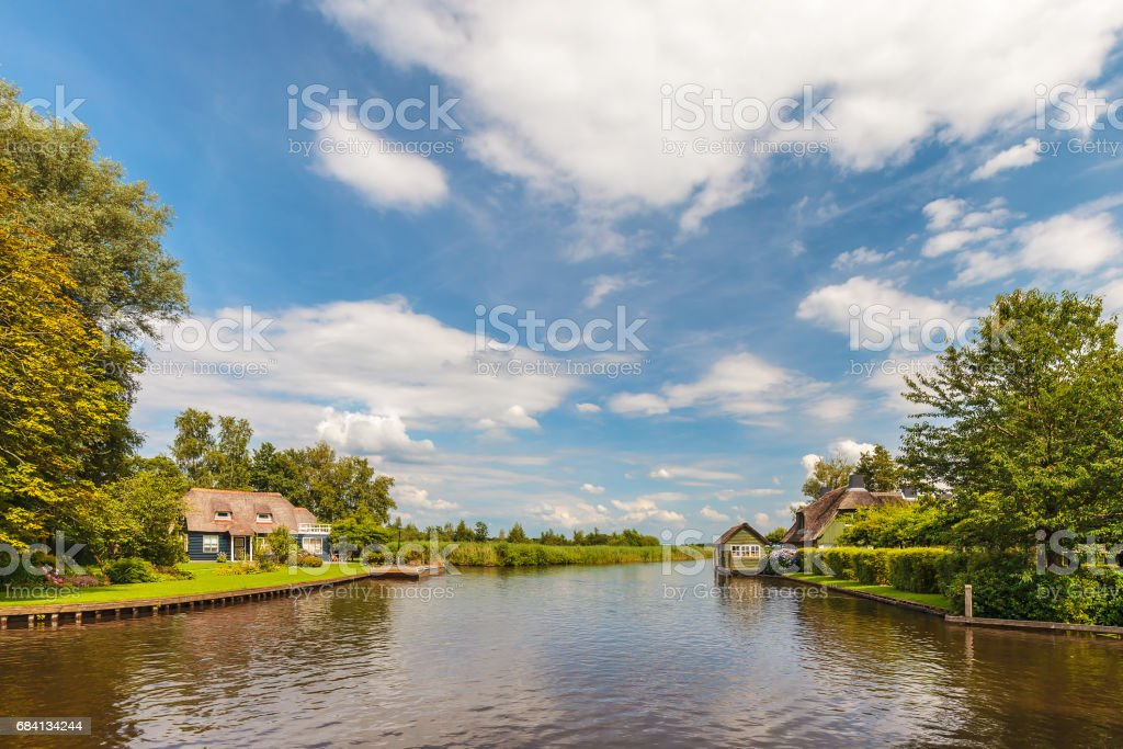 River with old houses in Dutch national park Weerribben royalty free stockfoto