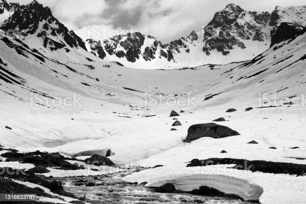 Photo of River with snow bridges in high snowy mountains at spring evening