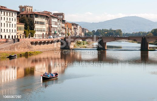 Florence, Italy - September 24, 2018: Riverboat with tourists floating past river Arno bridge of ancient Tuscany city on September 24, 2018. Historical Florence is a UNESCO World Heritage Site.