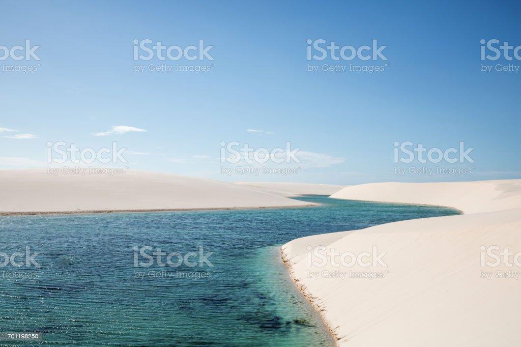 River-shaped lagoon among white sand dunes stock photo