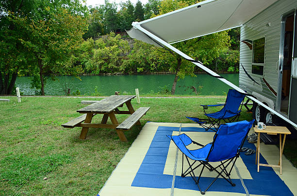 Riverside Campsite RV with lawn chairs and picnic table parked with river and trees in background.  Spring River, Hardy, Arkansas. awning stock pictures, royalty-free photos & images